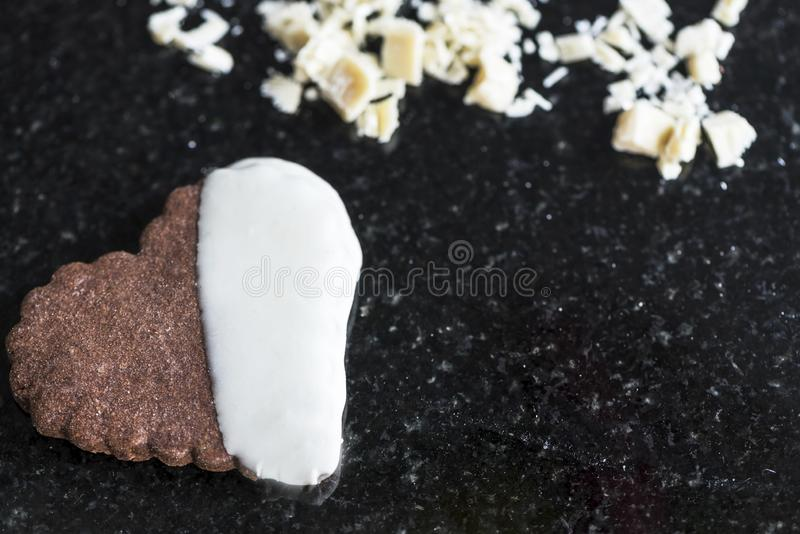 Whole heart shaped chocolate cookie with planed white chocolates on a black marble counter, close up royalty free stock photo