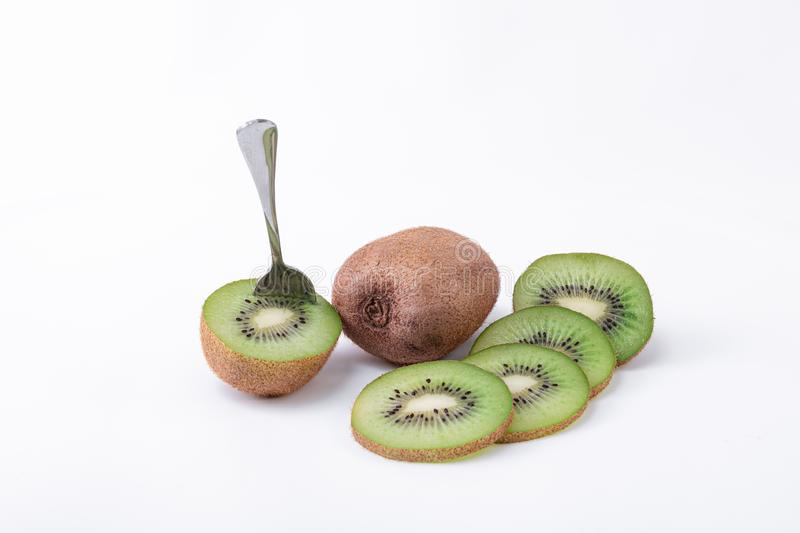 A whole kiwi, one cut in half with a spoon and slices of green kiwi with seed - Delicious fresh kiwi snack royalty free stock photo