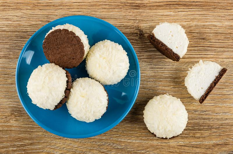 Whole marshmallows with coconut shaving in saucer, halves of cake on table. Top view. Whole marshmallows with coconut shaving in blue saucer, halves of cake on stock photos