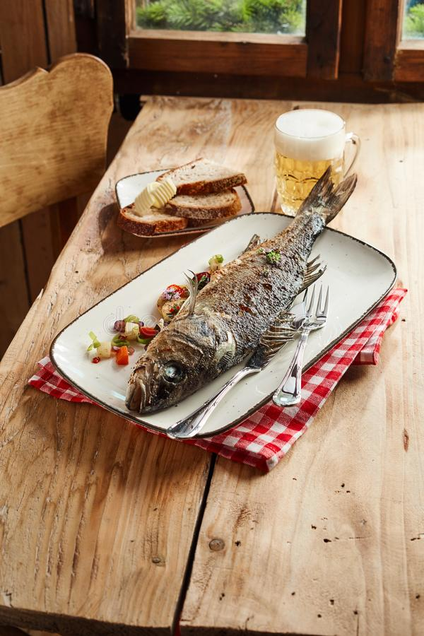 Whole oven roasted sea bass for a pub lunch. Served with a cold frothy beer and sliced rye bread with foreground copy space royalty free stock images