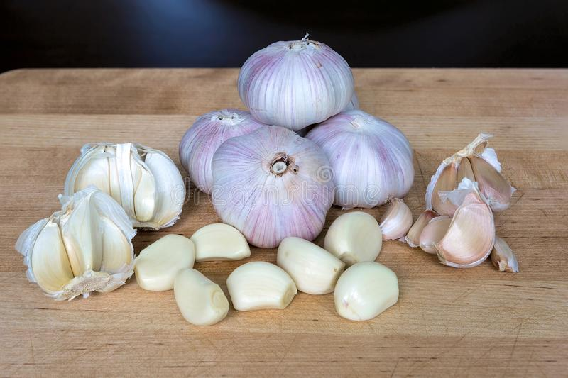 Whole and Peeled Garlic Cloves on Cutting Board royalty free stock images