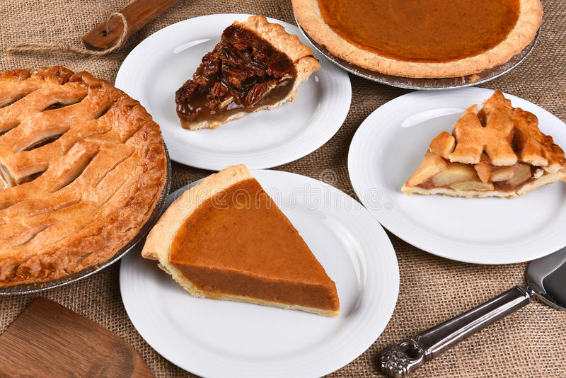 Whole Pies and Slices. High angle view of whole pies and plates with slices. Traditional Thanksgiving desserts include, Pecan Pie, Apple Pie and Pumpkin Pie royalty free stock photo