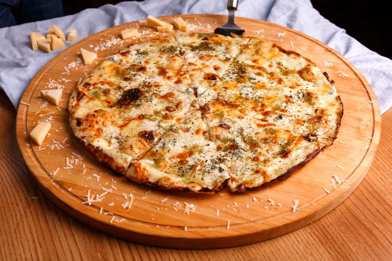 A whole pizza is served on the table royalty free stock image