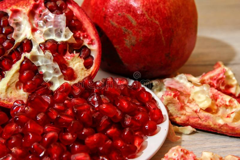 Whole pomegranate, part of pomegranate and pomegranate seeds stock photo