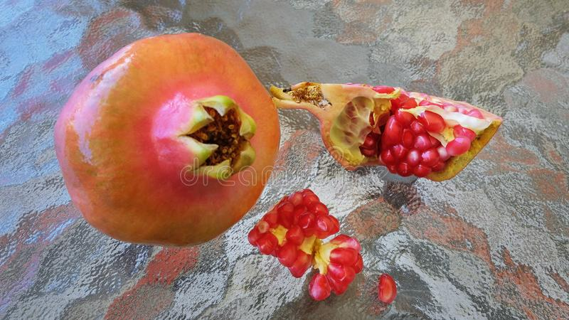 Whole pomegranate or Punica granatum fruit and few open pieces on an abstract glass surface. Whole pomegranate or Punica granatum fruit and few open pieces royalty free stock photos