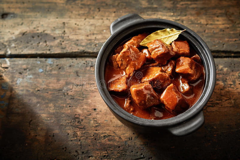 Whole pot of goulash in an aerial view. With copy space on brown wooden table stock image