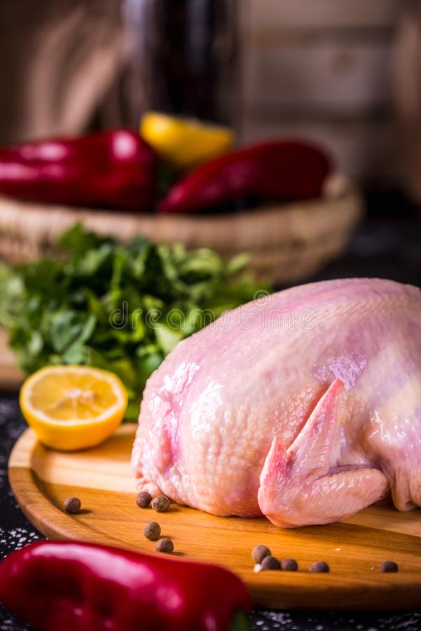 Whole raw chicken with rose pepper and lemon royalty free stock photos