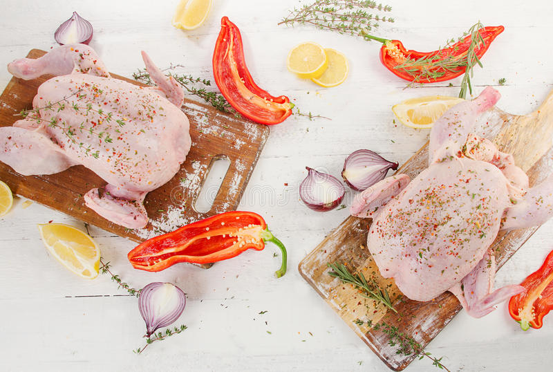 Whole raw chicken with spices and herbs on wooden table. stock image
