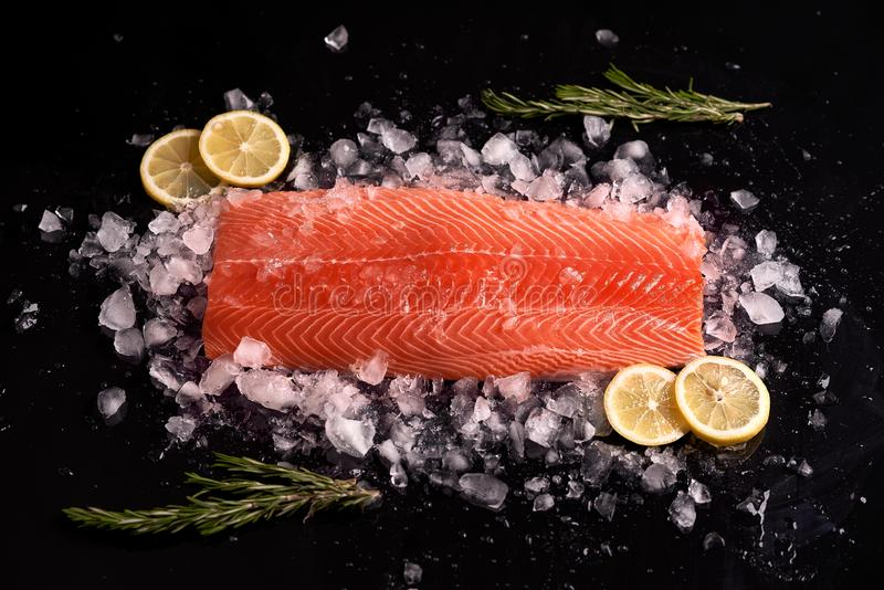 Whole raw red fish fillet with rosemary sprigs and lemon slices on a black background on a chipped ice. stock image