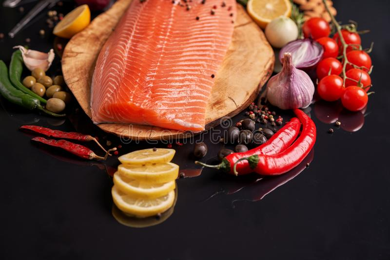 Whole red fish fillet on a wooden plate with cherry tomatoes, red and green chili peppers, black and green olives, lemon, garlic,. Peas and onions. Top view at royalty free stock image