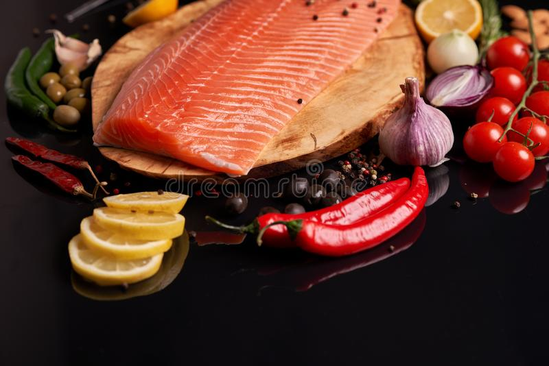 Whole red fish fillet on a wooden plate with cherry tomatoes, red and green chili peppers, black and green olives, lemon, garlic,. Peas and onions. Top view at royalty free stock images