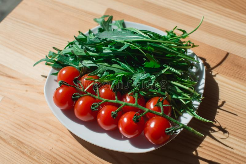 Whole red tomato cherry and fresh ruby leaves composition on a white plate on the wooden table royalty free stock image