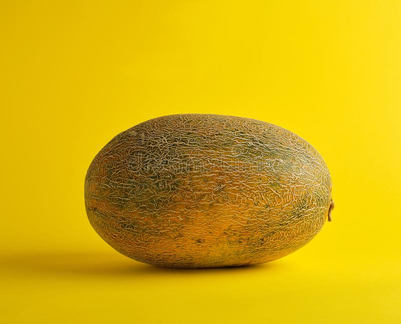 Whole ripe melon on a yellow background, summer fruit. Close up stock photos