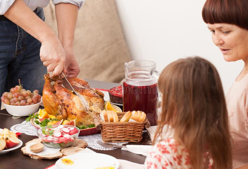 A man cuts baked the Turkey on the dining table royalty free stock images