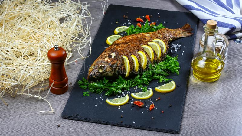 Whole roasted carp on slate plate with Text area for design menu restaurant royalty free stock photography