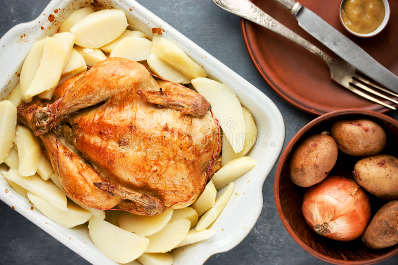 Whole roasted chicken with golden crust garnished potato royalty free stock photos