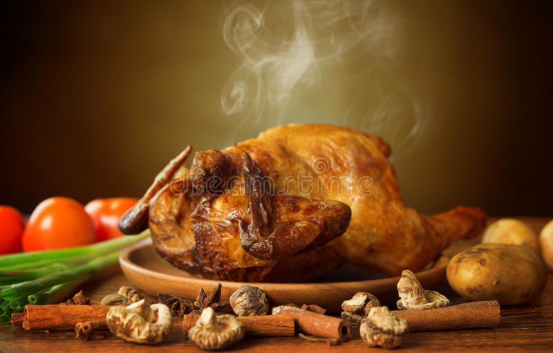 Whole roasted chicken with vegetables. On wooden tray fresh from oven with hot steam smoke, brown background stock images