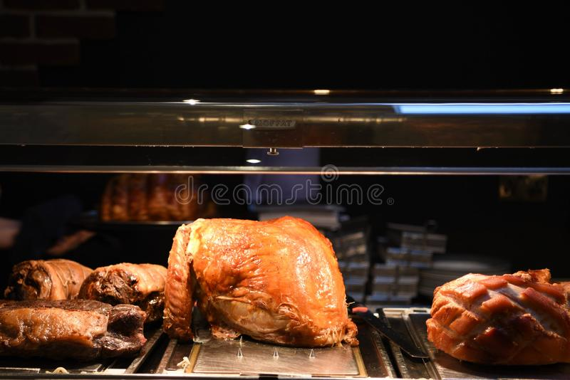 Golden roasted cooked whole turkey with gammon beef and lamb joints in the background royalty free stock image