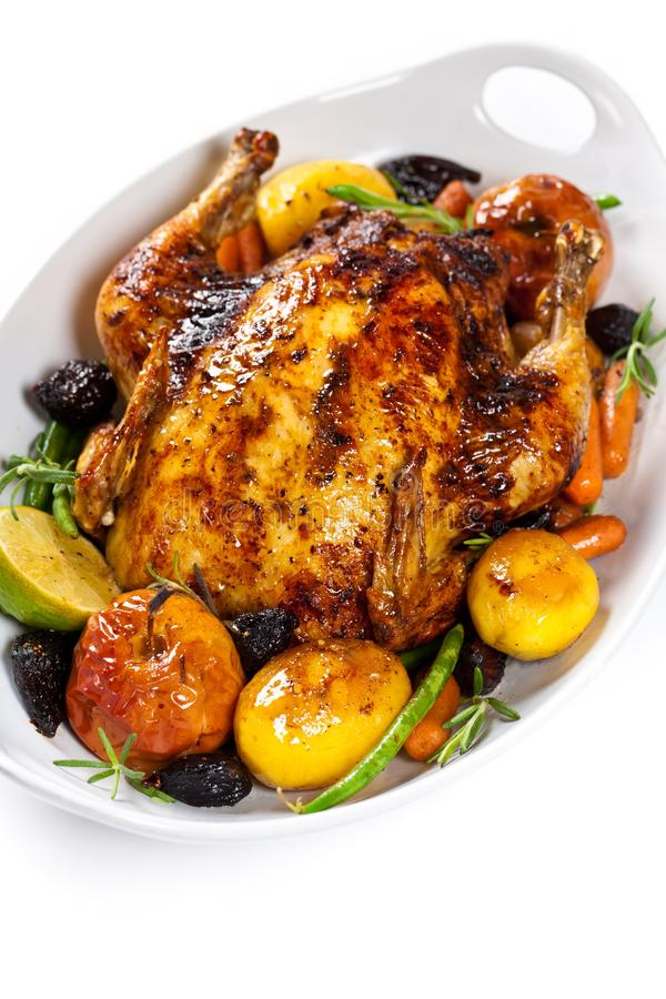 Whole Roasted holiday chicken. With Potatoes and Apples over white background royalty free stock photography