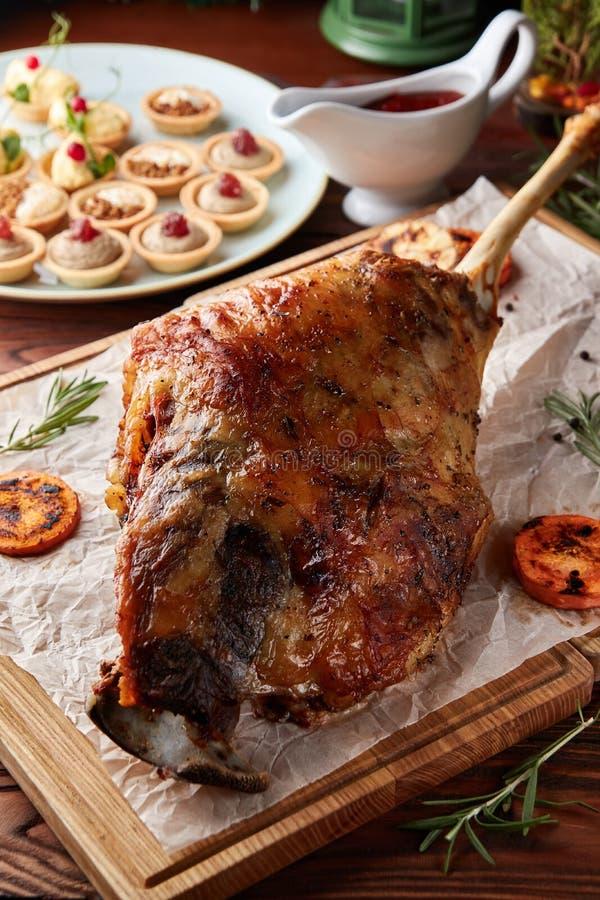 Whole roasted lamb leg on wooden cutting board stock photo