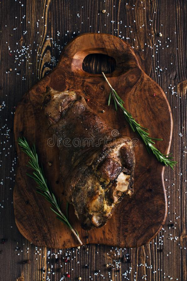Whole roasted pork knuckle with herbs. Whole roasted pork knuckle, wooden background royalty free stock photography
