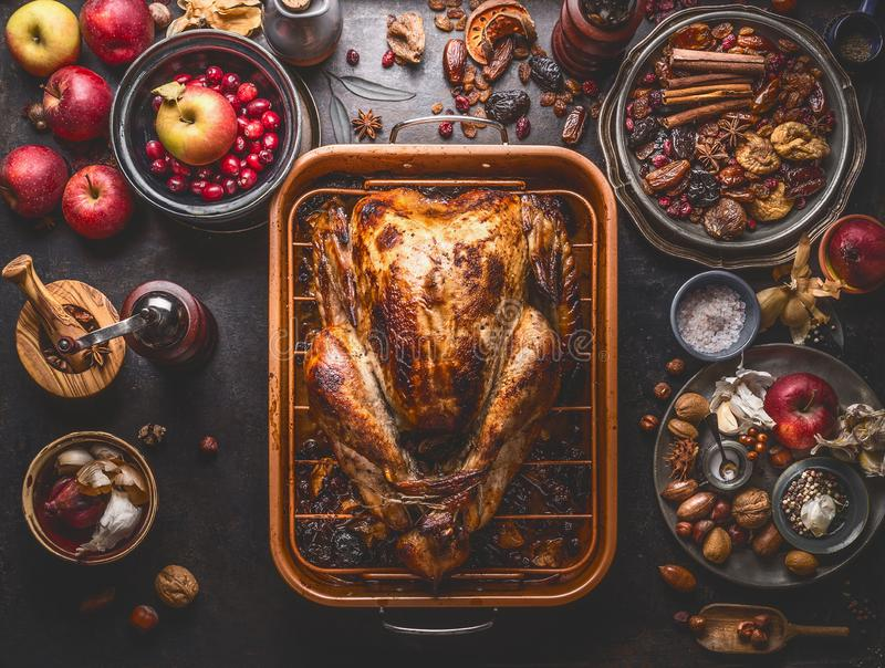 Whole roasted stuffed turkey in baking tray to Thanksgiving dinner on kitchen table with various autumn seasonal ingredients: stock images