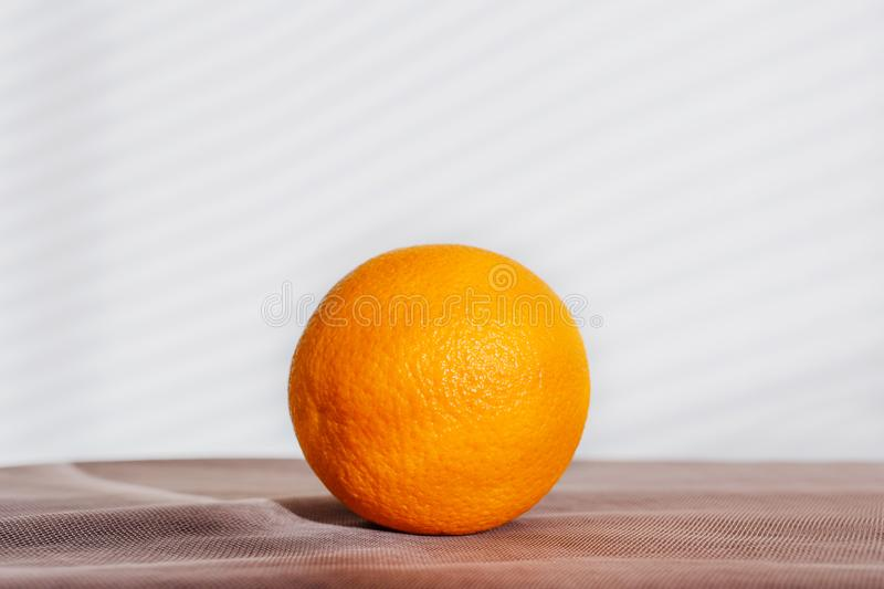 A whole round bright orange lies royalty free stock photography