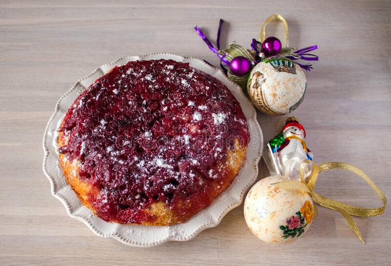 Whole round cranberry tart pie cake on white plate on wooden table background with christmas new year decoration stock photo