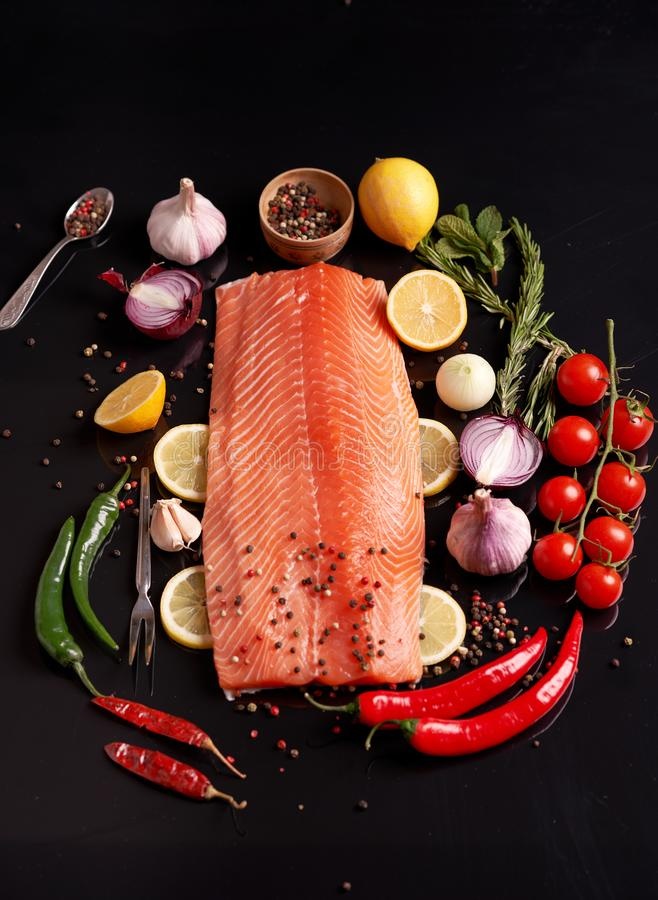 Whole salmon fillet on a dark reflective background with polka-dot colored pepper, garlic, lemon, rosemary, onion, cherry tomatoes stock image