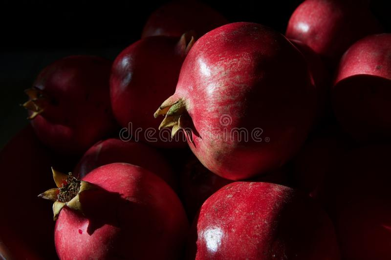 A whole scarlet pomegranate on a black background close-up royalty free stock photos