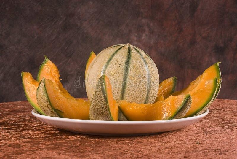 Whole and sliced cantaloupe royalty free stock photos