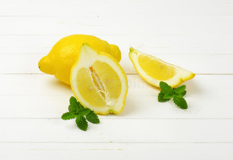 Whole and sliced lemons stock images