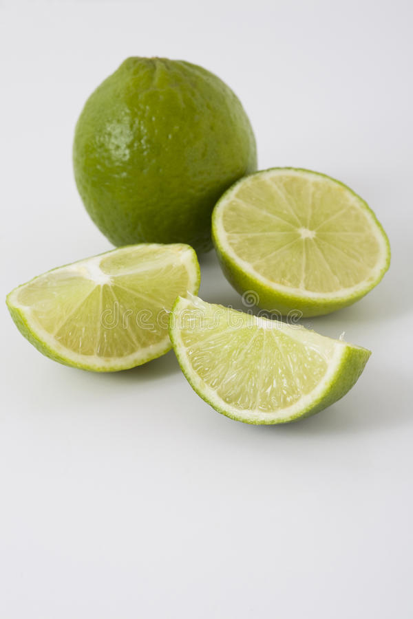 Whole and sliced limes. Closeup of whole and sliced limes on light surface stock images