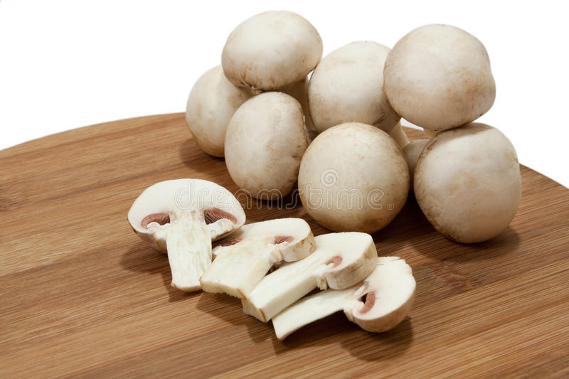 Whole and sliced mushrooms on wooden board.  royalty free stock photos
