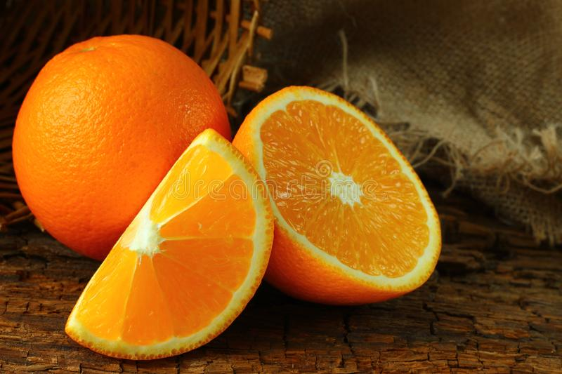 Whole, sliced oranges on a dark wooden background stock photos