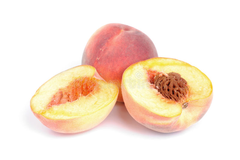Whole and sliced peach on white stock image