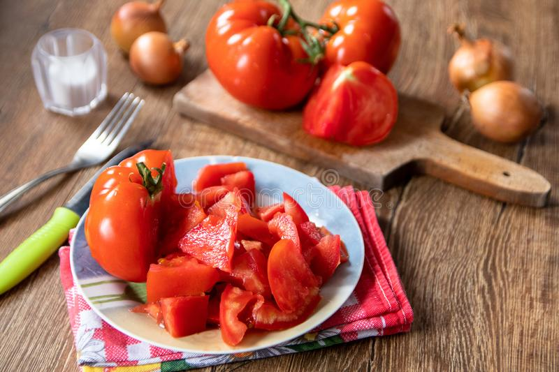 Whole and sliced tomatoes on cutting board and ceramic plate and whole onion in the background royalty free stock photography