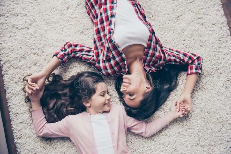 We are the only whole! Top view photo of cheerful friendly smiling mother and her daughter are lying on a carpet at home, holding stock photography