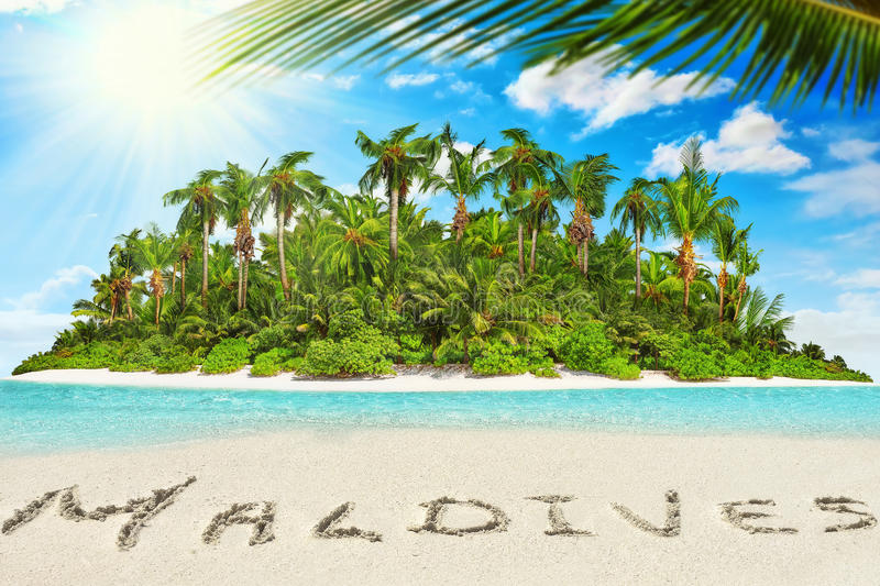 Whole tropical island within atoll in tropical Ocean and inscription 'Maldives' in the sand on a tropical island, Maldives. Whole tropical island within atoll stock photo