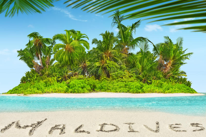 Whole tropical island within atoll in tropical Ocean and inscription 'Maldives' in the sand on a tropical island, Maldives. Whole tropical island within atoll stock photography