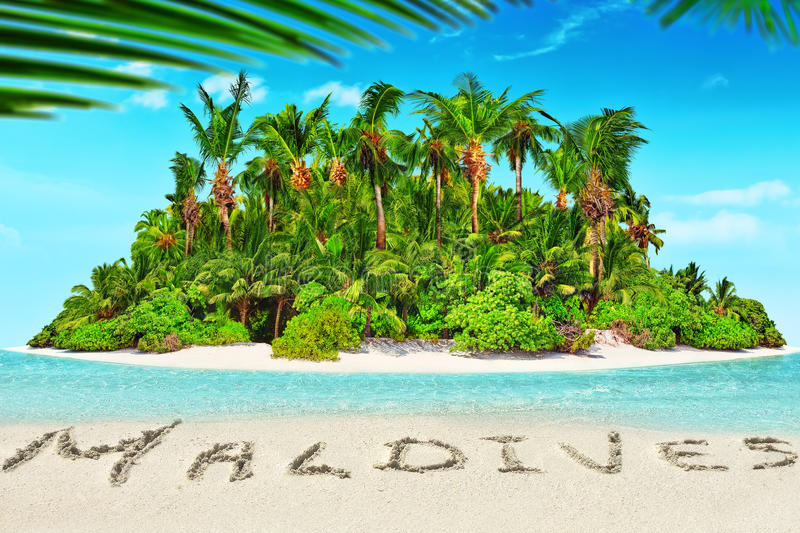 Whole tropical island within atoll in tropical Ocean and inscription 'Maldives' in the sand on a tropical island, Maldives. Whole tropical island within atoll stock photos