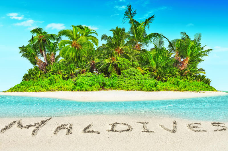 Whole tropical island within atoll in tropical Ocean and inscription 'Maldives' in the sand on a tropical island, Maldives. Whole tropical island within atoll stock image