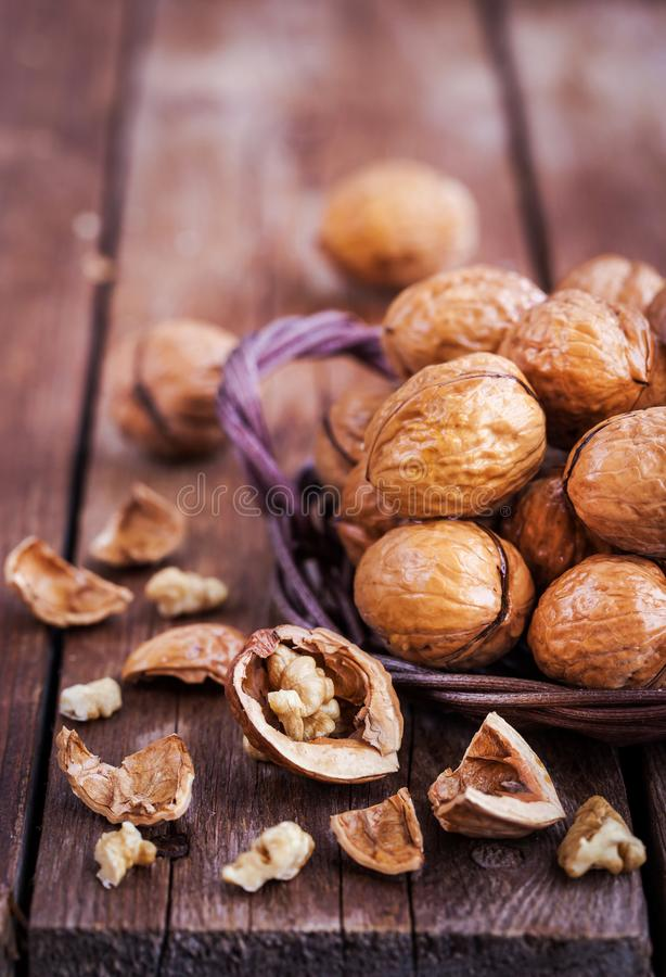 Whole walnuts in basket on rustic old wooden table royalty free stock images