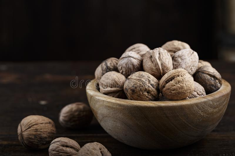Whole walnuts on a dark background. Inshell whole walnuts on dark wooden background. in a wooden plate stock photography