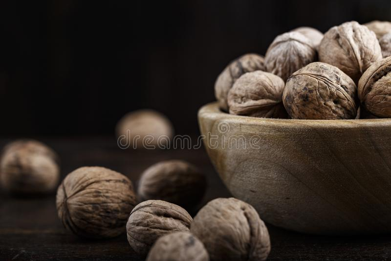 Whole walnuts place for text. Inshell whole walnuts on dark wooden background. in a wooden plate stock photography