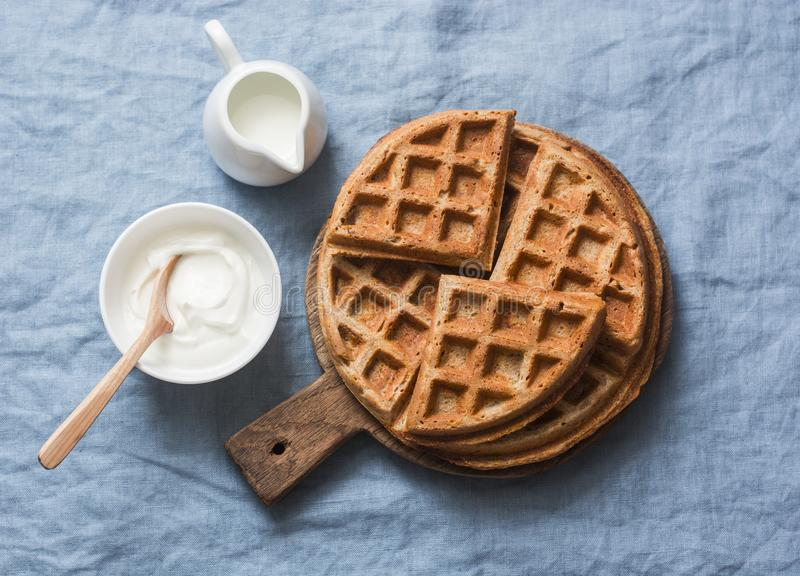 Whole wheat breakfast viennese waffles, cream and milk on blue background. Top view stock photo