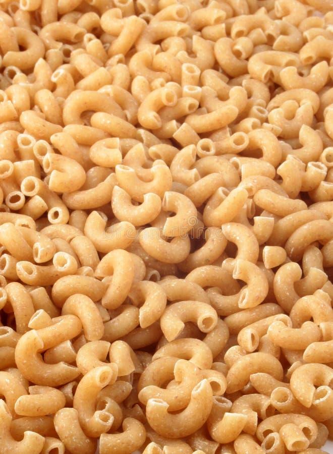Whole wheat macaroni. Pile of whole wheat macaroni pasta stock photo