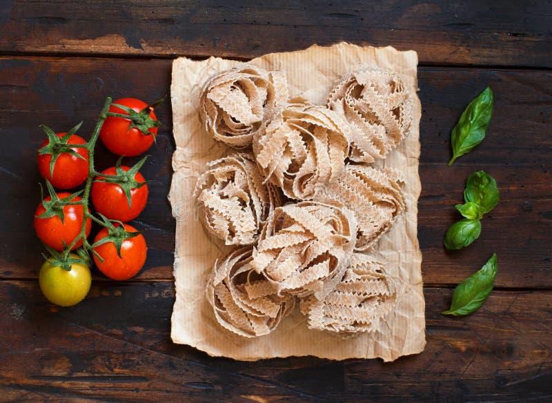 Whole wheat pasta tagliatelle, tomatoes and basil royalty free stock photos