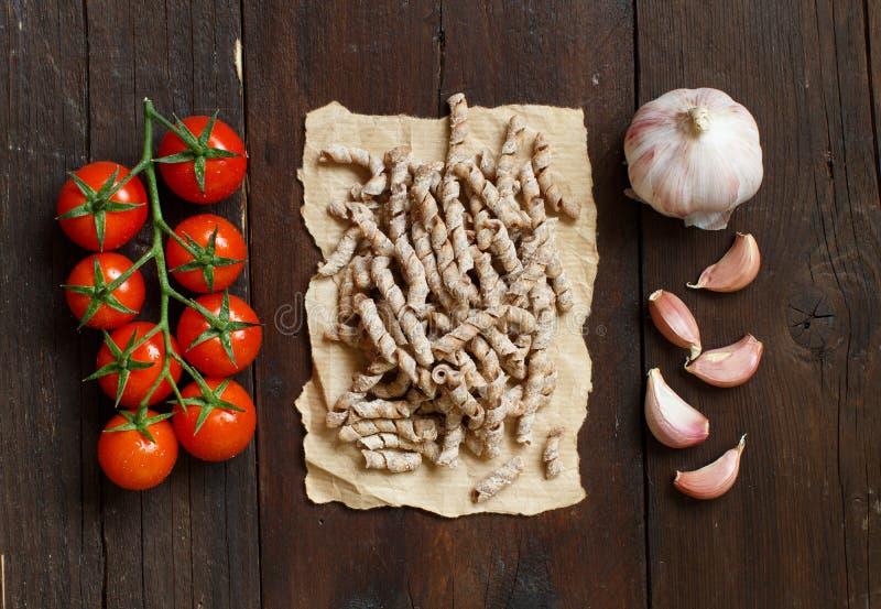 Whole wheat pasta, tomatoes and garlic stock image