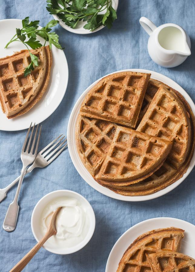 Whole wheat savory breakfast viennese waffles, cream and milk on blue background. Top view stock photo